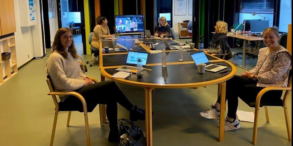 Medarbejderne i Opgang til Opgang holder møde om, hvordan tværfagligheden kan bruges konkret i familierne. Det er rundt om bordet Christina Lenon, Cand.Pæd.Psyk (forrest tv.), Saima Mushtaq, Uddannelseskonsulent (bagest tv.), Henriette Gaardbo, Foreningskonsulent (bagest th.), Tanja de Regt, Jobkonsulent (midten th.) og Jane Jensen, Familierådgiver (forrest th.) På skærmen med hjemmefra er Malene Post, Virksomhedskonsulent, Lene Madsen, Familierådgiver, Trine Krogh, Sundhedskonsulent, Mette Bødskov, Pædagog og Hani Balahang, Socialrådgiver Socialpsykiatri og udsatte voksne.